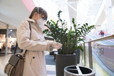 Woman with face mask removing disposable gloves in a shopping center - AHSF02595