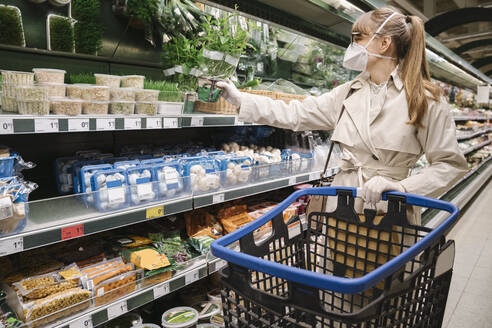 Woman with face mask and disposable gloves in a supermarket - AHSF02601
