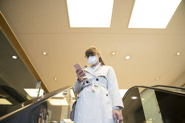 Woman with face mask using smartphone on an escalator in a shopping center - AHSF02604