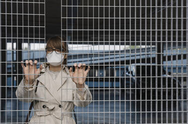 Woman wearing face mask standing behind grating in a car park - AHSF02610
