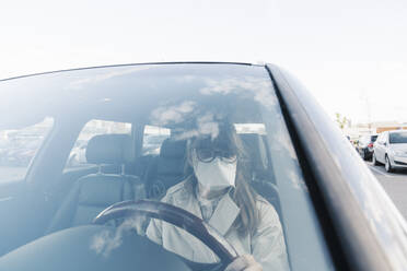 Woman wearing face mask in a car - AHSF02613