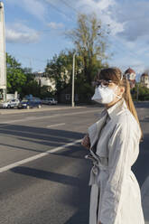Woman wearing face mask in the city - AHSF02616