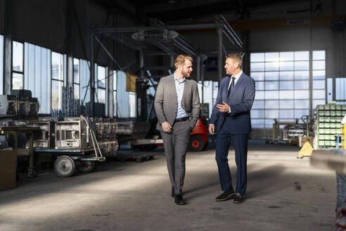 Two businessmen walking and talking in a factory - DIGF10988