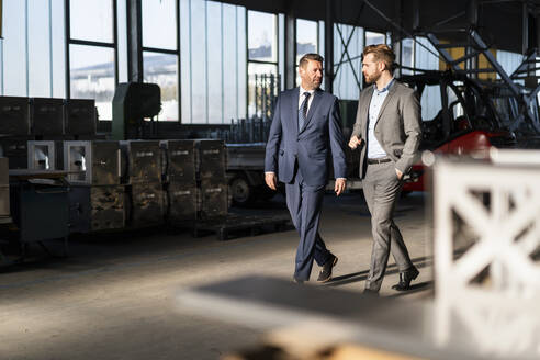 Two businessmen walking and talking in a factory - DIGF10994