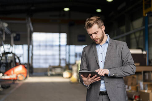 Young businessman using tablet in a factory - DIGF11033
