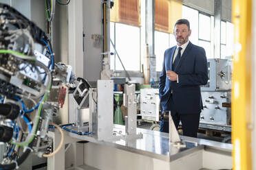 Mature businessman looking at a machine in a factory - DIGF11060