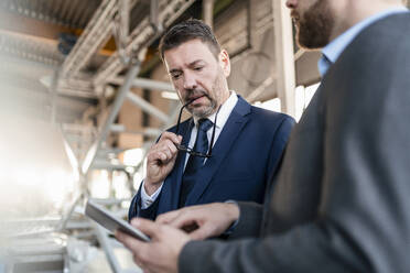 Two businessmen with tablet having a meeting in a factory - DIGF11069