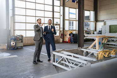 Two businessmen having a meeting in a factory - DIGF11075