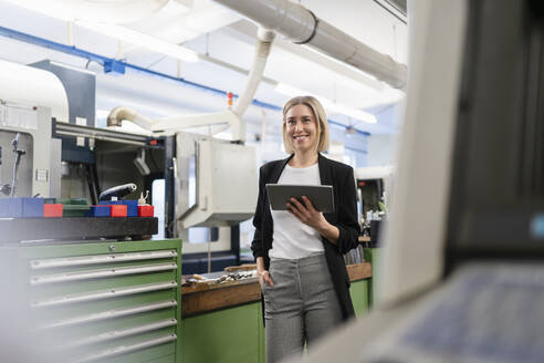 Smiling woman holding tablet in factory hall - DIGF11178
