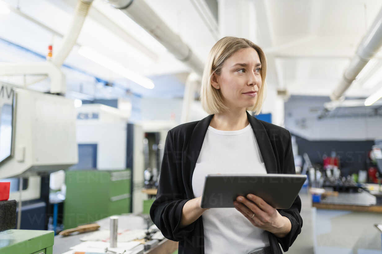 Woman holding tablet in factory hall looking around - DIGF11181 - Daniel Ingold/Westend61