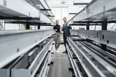 Businessman and woman at metal rods in factory hall - DIGF11229