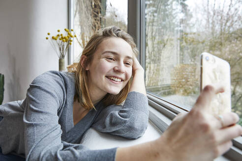 Portrait of happy young woman taking selfie with smartphone at home - FSF01079