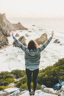 Young woman standing arms outstretched on rock at Ursa Beach, Lisboa Region, Portugal - FVSF00324