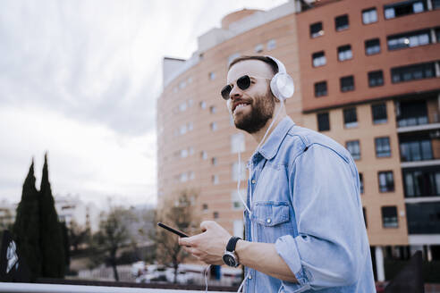 Portrait of smiling young man listening music with headphones and smartphone outdoors - EBBF00116