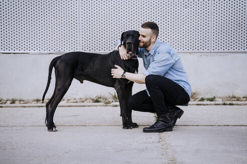 Happy young man cuddling his dog outdoors - EBBF00119