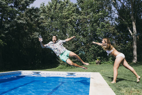 Playful young woman pushing boyfriend in swimming pool against trees - ABZF03141