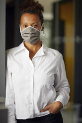 Portrait of businesswoman wearing homemade protective mask - RBF07687