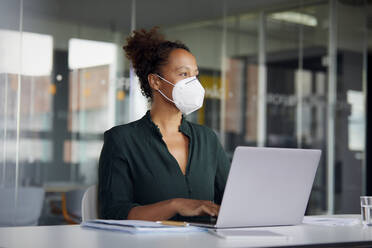 Portrait of businesswoman wearing  protective mask working on laptop at counter looking at distance - RBF07708