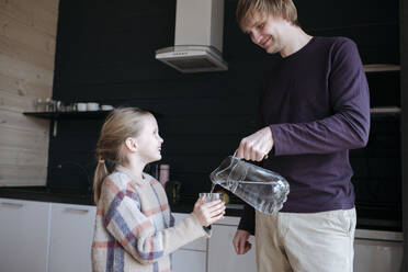 Father pouring water into glass for his smiling daughter in the kitchen - EYAF01069