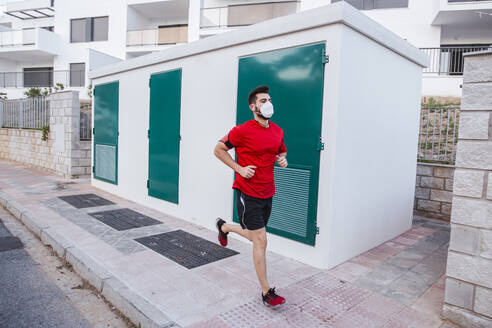 Mid adult man wearing face mask while running on footpath in city - LJF01527