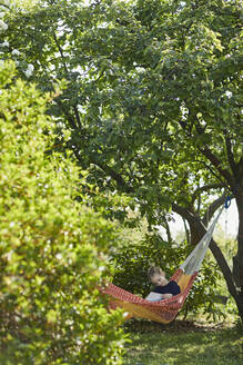 Girl in hammock reading a book - MCF00836