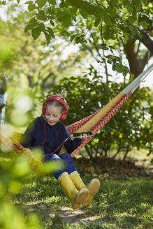 Girl with smartphone and headphones in hammock listening to music - MCF00839