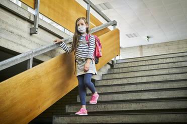 Girl wearing mask in school walking down stairs - DIKF00509