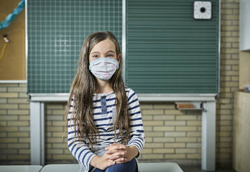 Portrait of girl wearing mask in classroom - DIKF00512
