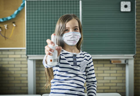 Portrait of girl wearing mask in classroom spraying sanitizer - DIKF00515