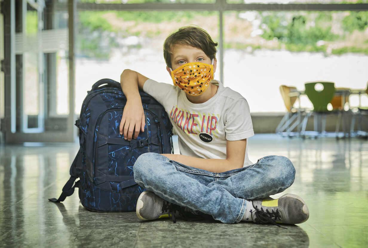 Boy sitting on the floor in school wearing mask - DIKF00518 - Dirk Kittelberger/Westend61
