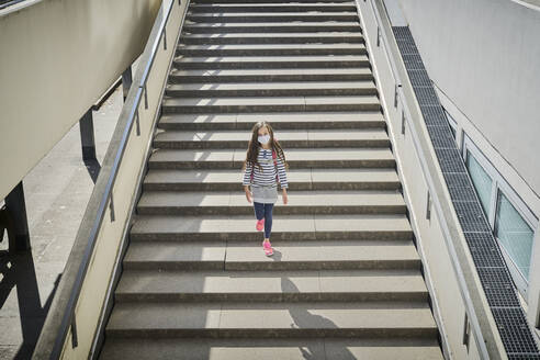 Girl wearing mask and schoolbag walking on stairs - DIKF00524