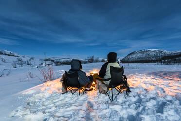 Campers at camp fire in winter landscape in polar night, Kilpisjaervi, Enontekioe, Finland - WVF01532