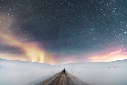 Man standing on country road under starry sky with northern lights, Lebesby, Norway - WVF01619