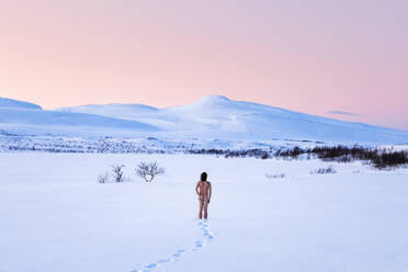 Nude man standing in winter landscape, Lebesby, Norway - WVF01646
