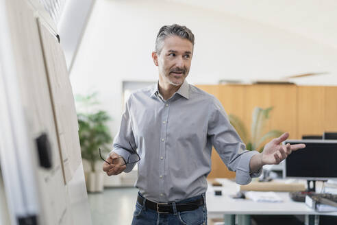 Confident mature male entrepreneur explaining strategy while standing by whiteboard in office - DIGF11268