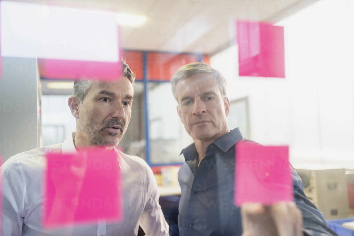 Mature businessmen discussing over adhesive notes on glass at office during meeting - DIGF11274 - Daniel Ingold/Westend61