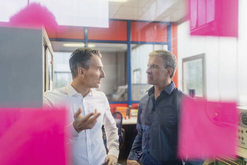 Confident male business partners planning strategy while standing in office during meeting - DIGF11277