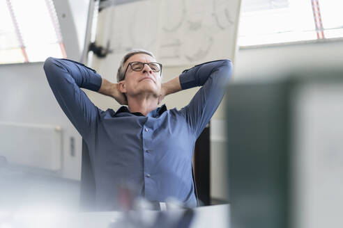 Tired mature male professional relaxing while sitting with hands behind head at office - DIGF11301