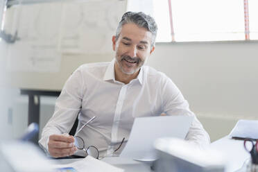 Smiling handsome male professional sitting with paper at desk in office - DIGF11313