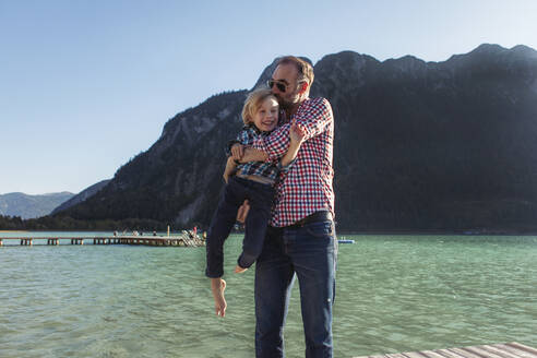 Father kissing while carrying son against mountain at Achensee, Tyrol State, Austria - JLOF00392