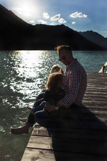 Father sitting with children on boardwalk by lake at Achensee, Tyrol State, Austria - JLOF00401
