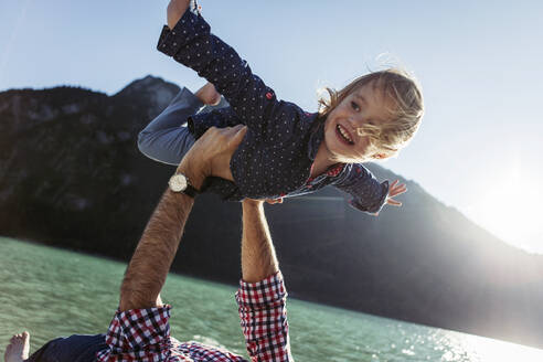 Happy girl with arms outstretched being carried by father at Achensee, Tyrol State, Austria - JLOF00407