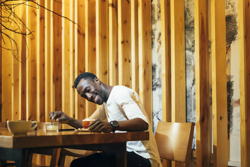 Smiling young man looking at coffee on table while sitting against wall in cafe - OCMF01256