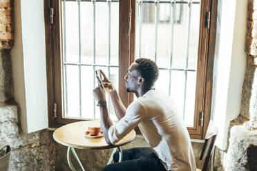 Madrid Spain, african man in coffee shop - OCMF01259