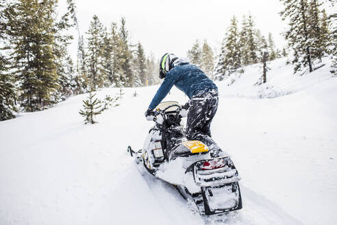 Rear view of man snowmobiling in winter weather. - CAVF82036