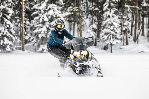 Skilled snowmobiler stands on side, preparing for powder turn. - CAVF82042
