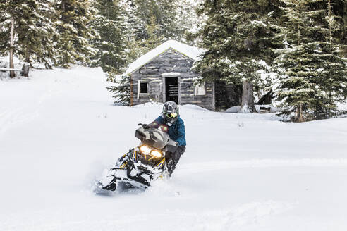 Confident man on snowmobile with old cabin behind. - CAVF82045