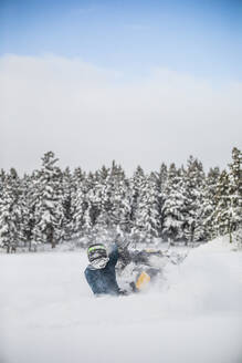 Rear view of experienced rider snowmobiling through powder snow. - CAVF82048