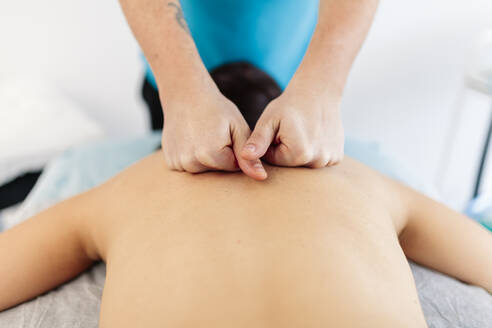 Visually impaired physiotherapist massaging woman's back in clinic - MRRF00048