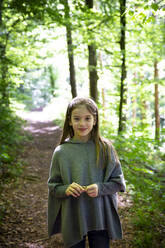 Portrait of smiling girl standing on hiking trail against trees in forest - LVF08903